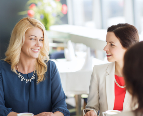 three women meeting and talking at restaurant