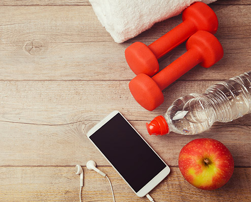 group of fitness items on the ground - smartphone, water bottle, apple, weights, towel