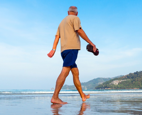 elderly man with joint replacement walking on the beach